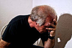 Distressed man  holding head. Portrait of a distressed older white man holding head sitting in corner of white room Royalty Free Stock Photo