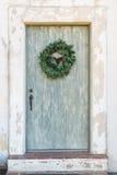 Distressed narrow front door. Vintage front door with wreath Stock Image