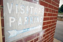 Distressed Visitors Parking Sign on an old brick wall. stock photography