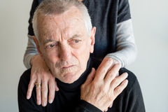 Distressed older man. Distressed older men with short grey hair and black top being comforted by older women (selective focus Royalty Free Stock Image