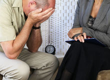 Distressed patient. Female counselor with distressed male patient holding head in hands seated royalty free stock image