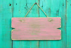 Distressed pink blank sign hanging on antique green wooden door Royalty Free Stock Photos
