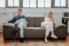 Distressed short-haired man sitting far away from his upset wife. Wife sitting nearby. Distressed short-haired men sitting far away from his upset wife while royalty free stock photography