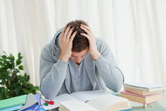 Distressed student in front of his books Stock Photography