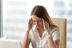 Distressed unhappy businesswoman suffering from headache, massag. Distressed unhappy businesswoman suffering from strong headache, massaging temples, depressed Royalty Free Stock Image