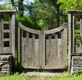 Distressed Wood Gate with Stacked Stone, Grass and Trees. Stock Images