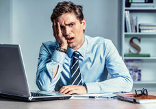 Distressed young man holds his head with hand. Modern businessman at the workplace, depression and crisis concept Stock Photo