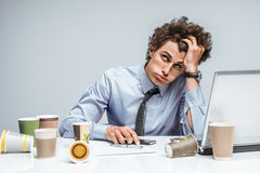 Distressed young manager man holds her head with hand. Modern office man at working place, depression and crisis concept Royalty Free Stock Images