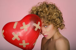 Distressed young woman with ball in shape of heart Stock Photography