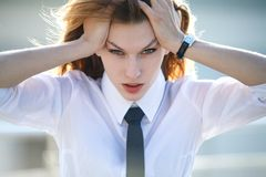Distressed young woman holds her head with both ha stock photo
