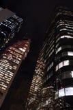 Distretto finanziario delle costruzioni alte del grattacielo alla notte, vista di angolo basso, verticale Immagini Stock