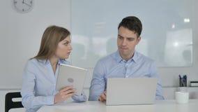 Distribución de opiniones, de colegas del negocio usando la tableta y del ordenador portátil durante trabajo almacen de metraje de vídeo