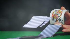 Distribuição do negociante cartões na tabela verde do pôquer com efeitos da luz vídeos de arquivo