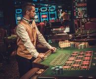 Distribuidor autorizado detrás de la tabla en un casino foto de archivo