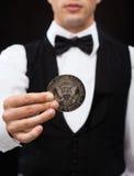 Distribuidor autorizado que sostiene la moneda del medio dólar Foto de archivo libre de regalías