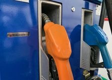 Distributeur d'huile remplissant huile dans la station d'huile, orange et bleu photos stock