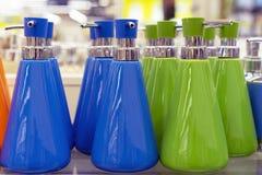 Distributeurs pour le savon liquide de diverses couleurs sur le rayon de magasin photo libre de droits