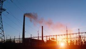 Distributie elektrisch hulpkantoor met machtslijnen en transformatoren, bij zonsondergang stock afbeeldingen