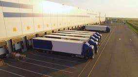 Distributiepakhuis met vrachtwagens die op lading wachten stock footage