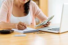 Distributing family budget. Woman distributing family budget at home stock photo