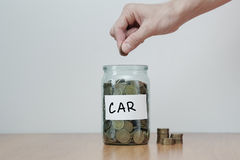 Distribution of cash savings concept. Hand puts coins to the glass money boxes with inscription `car`. Distribution of cash savings concept. Hand puts coins to Stock Photo