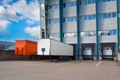 Distribution Center with Trailers. Red and White Trailer at a Docking Bay of a distribution centre, ready for Transport stock photography
