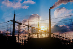 Distribution electric substation with power lines and transformers, at sunset. Stock Image