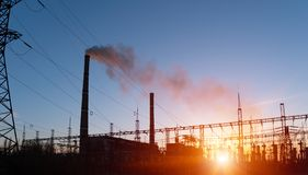 Distribution electric substation with power lines and transformers, at sunset.  stock images
