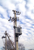 Distribution electrical transformer mounted on a pole. Electric Royalty Free Stock Image