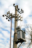 Distribution electrical transformer mounted on a pole. Electric Royalty Free Stock Images