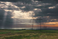 Distribution pylons with high voltage wires at sunrise. Distribution poles with high voltage wires, early in the morning with dramatic sky and sun rays that Royalty Free Stock Photos