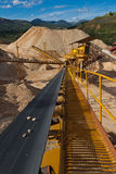 Distribution and Screening Plant Gravel. Machinery and classification according gravel size distribution via conveyor belts  in mountainous landscape with piles Royalty Free Stock Images