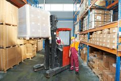 Distribution in warehouse. Worker and manager distributing goods in a warehouse with forklift truck loader Royalty Free Stock Image