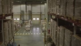 Distribution Warehouse Interior. Shelves and racks in distribution warehouse interior.Rows with cardboard boxes and goods at shelves.Logistic, transportation and stock footage