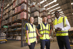 Distribution warehouse manager and colleagues look to camera stock photo