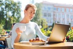 Distributions d'articles Usenet avec du charme de lecture de femme en café Photo stock