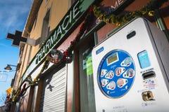 Distributore commerciale del preservativo davanti ad una farmacia nel centro urbano immagine stock