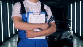 Distributore di benzina e un tecnico maschio che sta con una lavagna per appunti e gli strumenti Servizio dell'automobile, concet archivi video