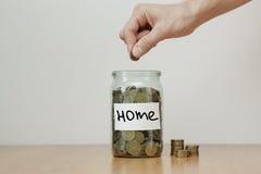 Distribuzione del concetto di risparmio dei contanti La mano mette le monete ai salvadanai di vetro con il ` della casa del ` del Fotografia Stock