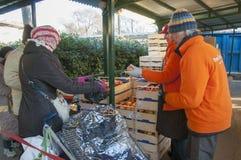 Distribuzione di cibo en personepovere` förser med rutor quotidiano`, royaltyfri foto