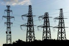 Distribuzione di elettricità con le linee elettriche ad alta tensione fotografia stock