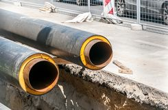 District heating insulated pipes pipeline reparation and reconstruction parallel with the street with construction site metal safe. Ty net fence stock images