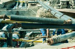 District heating pipeline reparation and reconstruction parallel with the street with construction site safety net fence. District heating pipeline reparation Royalty Free Stock Image