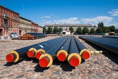 District heating pipes. The row of the new factory preinsulated district heating pipes lay on the pavement ground to be installed while reconstruction process Royalty Free Stock Image
