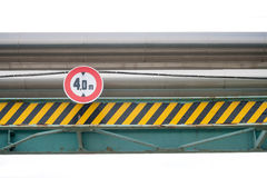 District-heating system pipes. Above street with a trafic sign of maximum vehicle height and architectural metalwork Royalty Free Stock Photography