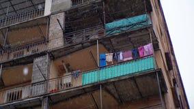 Districto pobre de la ciudad Ropa que cuelga en una cuerda para tender la ropa en un edificio durante la lluvia metrajes