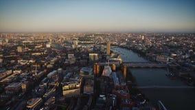 Distrito céntrico ocupado de la arquitectura moderna de Londres por el río Támesis en panorama aéreo de la puesta del sol del abe almacen de metraje de vídeo