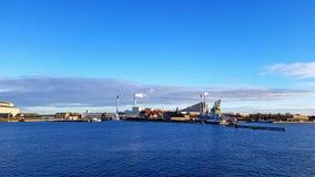Distrito da área industrial de Copenhaga ao longo do mar com o céu azul claro durante o tempo do por do sol imagem de stock
