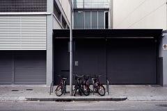 Distrito industrial com armazém cinzento, espaço vazio da parede para a disposição de projeto e estacionamento da bicicleta na ru imagem de stock royalty free
