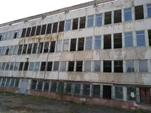 Distroyed przemysłowy budynek z łamanymi okno charcica zdjęcia stock